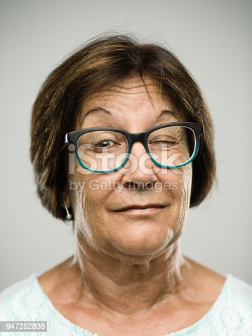 Close up portrait of hispanic mature woman with one eye closed against gray background. Vertical shot of real senior woman winking and blinking in studio. Short brown hair and modern glasses. Photography from a DSLR camera. Sharp focus on eyes.
