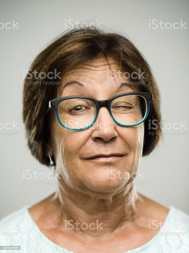Real senior woman portrait winking stock photo