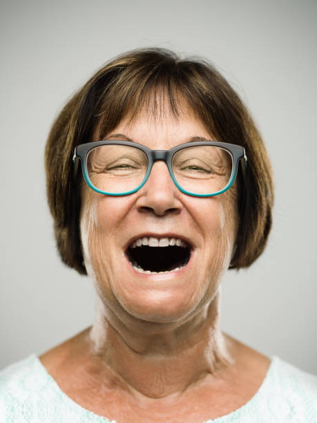 Real shouting senior woman portrait Close up portrait of hispanic mature woman with shouting expression against white background. Vertical shot of real senior woman screaming in studio. Short brown hair and modern glasses. Photography from a DSLR camera. Sharp focus on eyes. mouth open stock pictures, royalty-free photos & images