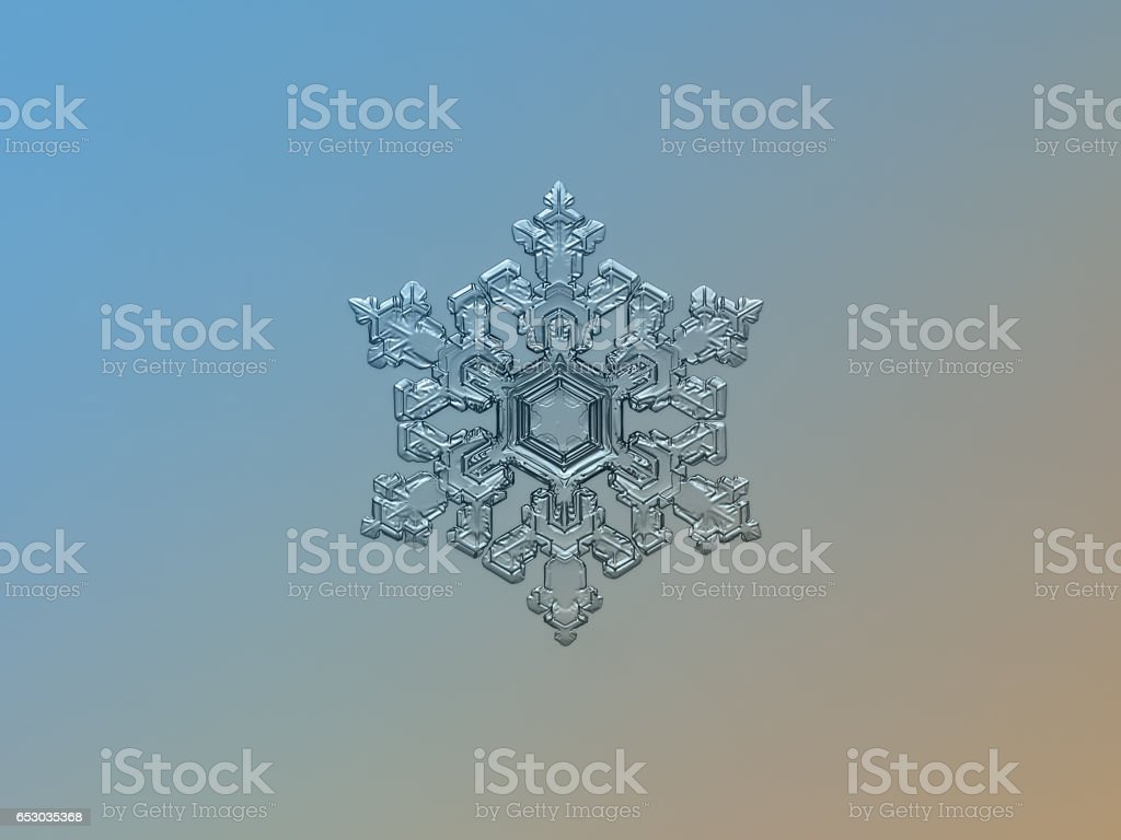 Real snowflake sparkling on smooth gradient background stock photo