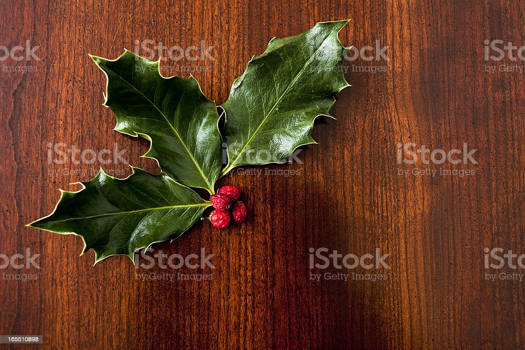 Real, Traditional Holly on Wood Grain Table royalty-free stock photo
