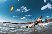 Real wakeboarder with yellow kite rides at sea bay