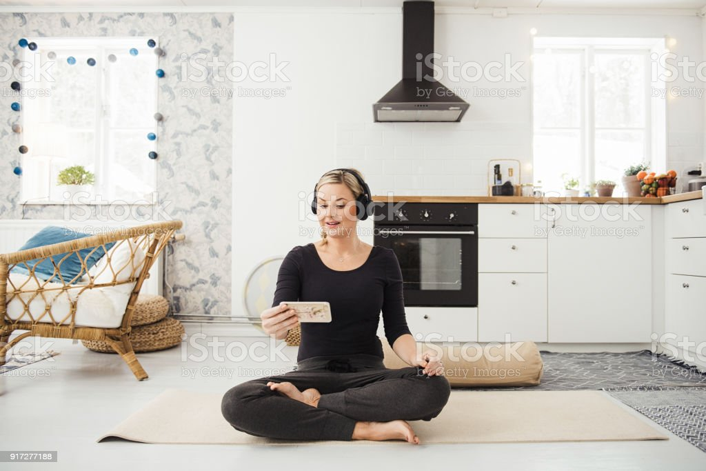 Real woman at home in kitchen doing yoga and meditation stock photo
