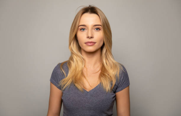 Real woman. Close up photo of a charming girl with fair hair, who is looking in the camera with calm facial expression. blond hair stock pictures, royalty-free photos & images