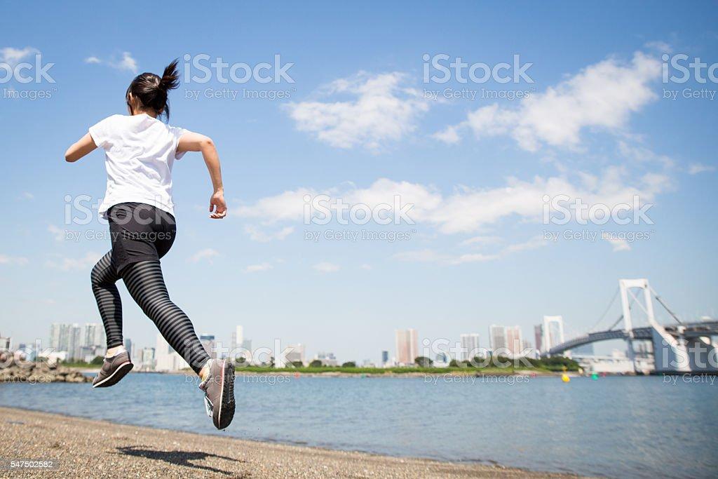 Real woman running near the beach stock photo