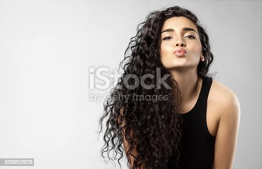 istock Real woman with beauty black hair gives a kiss 539953926