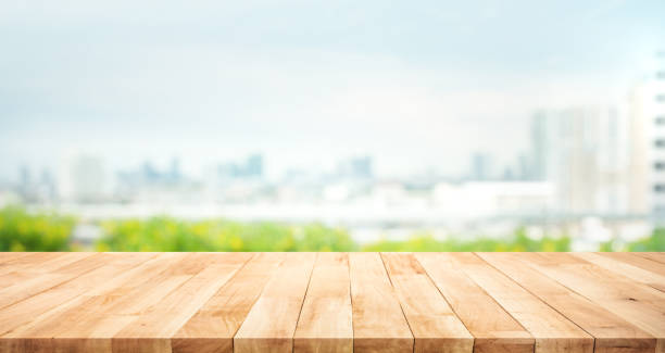 Real wood table top texture on blur leaf tree garden and wall building from city,park background stock photo