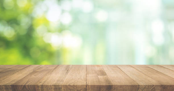 Real wood table top texture on blur leaf tree garden background. stock photo