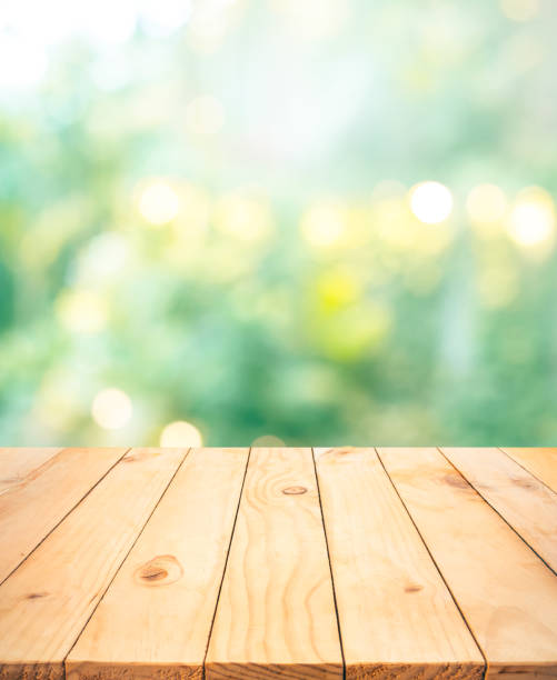 Real wood table top texture on blur leaf tree garden background stock photo