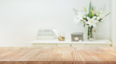 Real wood table top texture on white wall room background.