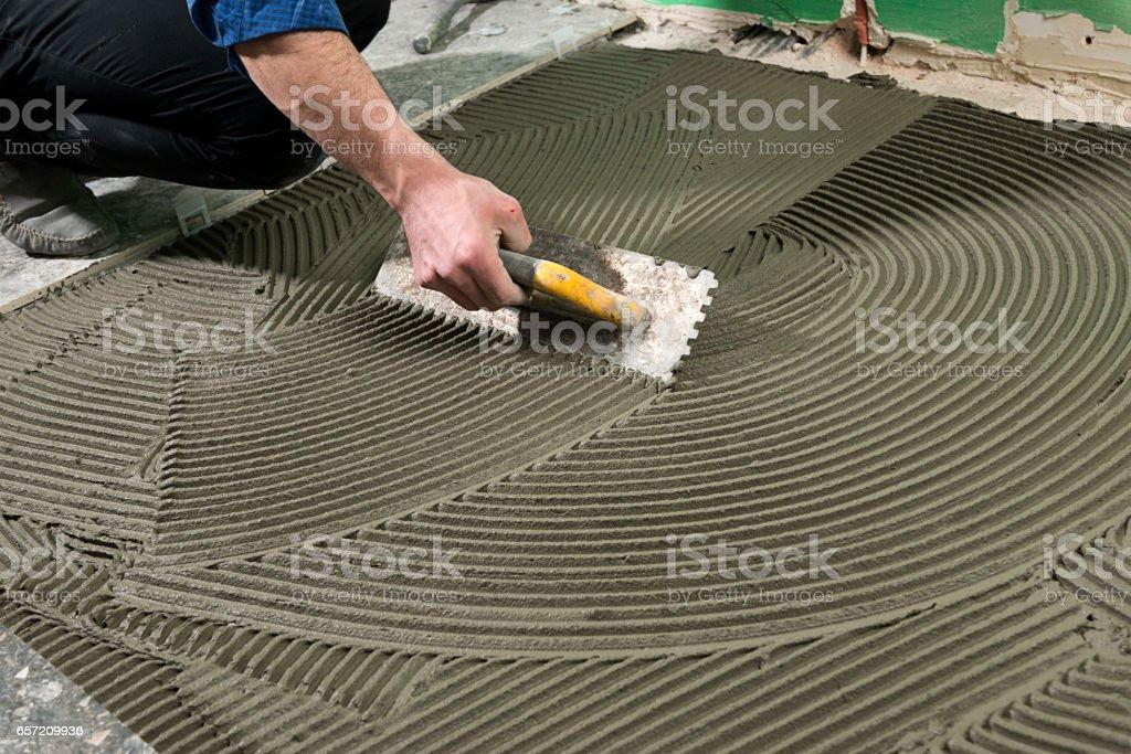 Real Worker Applying Ceramic Glue stock photo