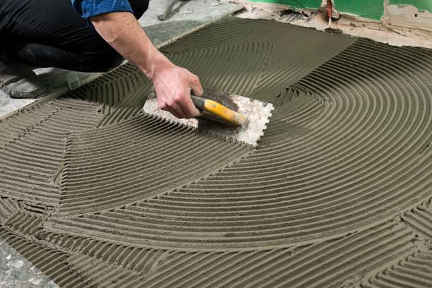 echte arbeiter anwenden keramik kleber - fliesenkleber stock-fotos und bilder