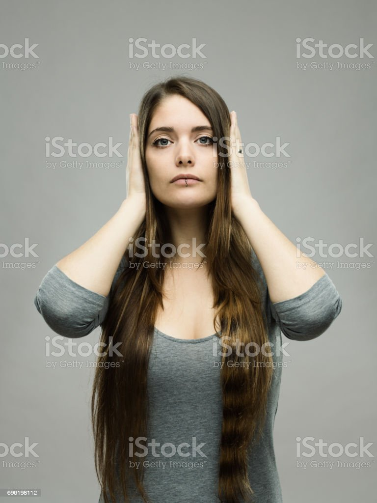Real young woman covering her ears stock photo
