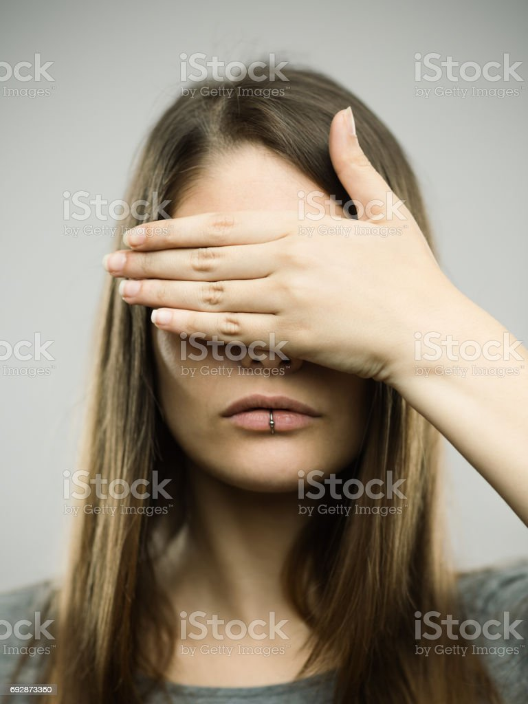 Real young woman covering her eyes stock photo