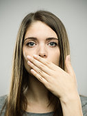 Close-up portrait of beautiful young woman covering her mouth with the hand. Real people female is against gray background with speak no evil gesture. She has long brown hair. Vertical studio photography from a DSLR camera. Sharp focus on eyes.