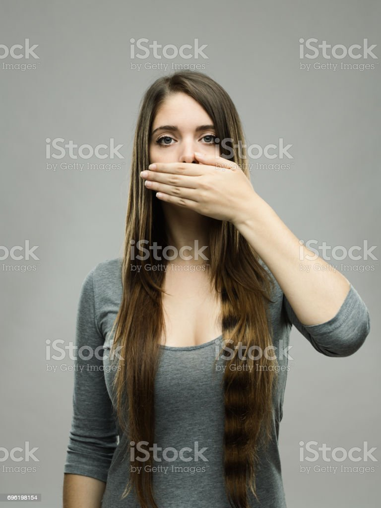 Real young woman covering her mouth stock photo
