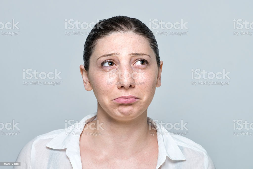 real young woman sad portrait isolated on grey stock photo