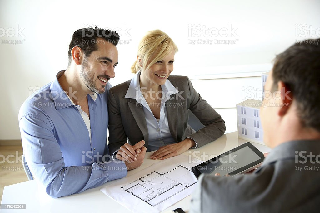Real-estate agent giving information to couple on tablet Couple meeting real-estate agent to buy property Adult Stock Photo