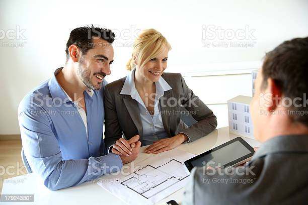 Realestate Agent Giving Information To Couple On Tablet Stock Photo - Download Image Now