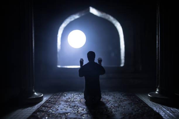 A realistic Arabian interior miniature with window and columns. Silhouette of muslim praying on carpet near window. Festive greeting card, invitation for Muslim holy month Ramadan Kareem. – zdjęcie