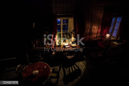 A realistic dollhouse living room with furniture and window at night. Man sitting on table in dark room. Selective focus.