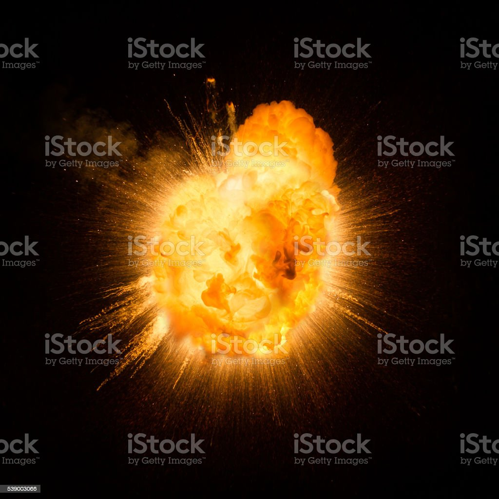 Realistic fiery explosion busting over a black background stock photo