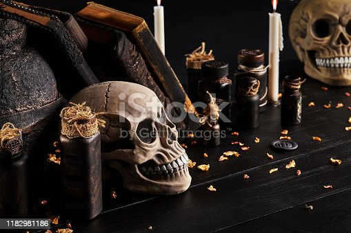 1176385551istockphoto Realistic model of a human skull with teeth on a wooden dark table, black background. Medical science or Halloween horror concept. Close-up shot 1182981186