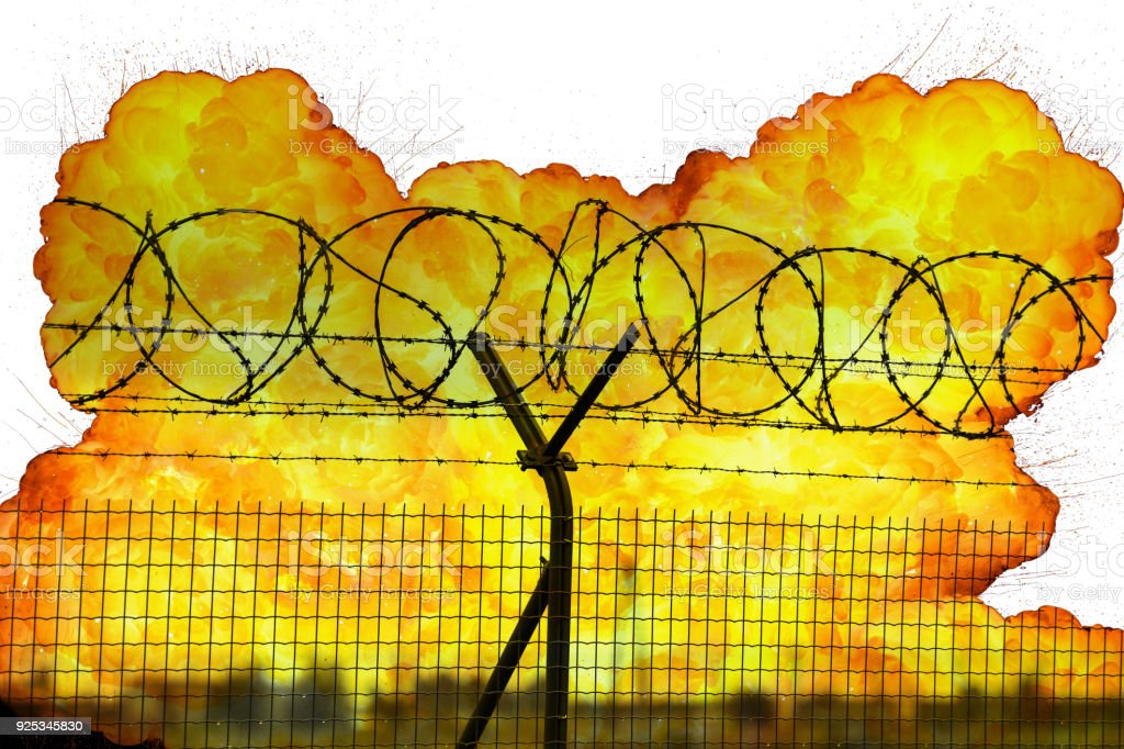 Realistic orange fire explosion behind restricted area barbed wire fence isolated on white background stock photo