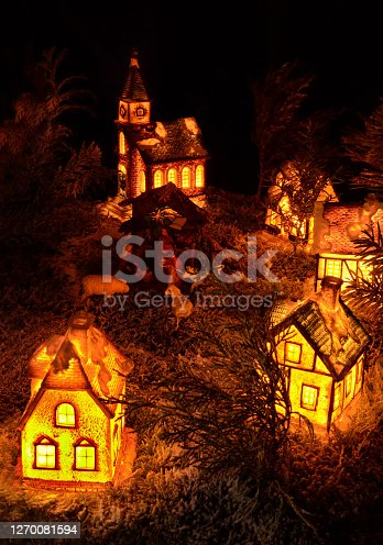 istock Realistic Xmas decoration from miniature ceramic houses, little creche, trees and Christian church 1270081594