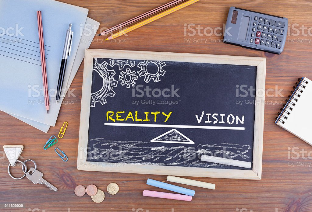 Reality and Vision Balance. Chalkboard on wooden office desk stock photo