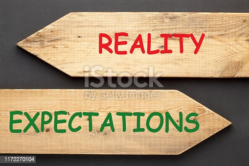 The words Reality vs. Expectations written on old wooden arrows on black background.