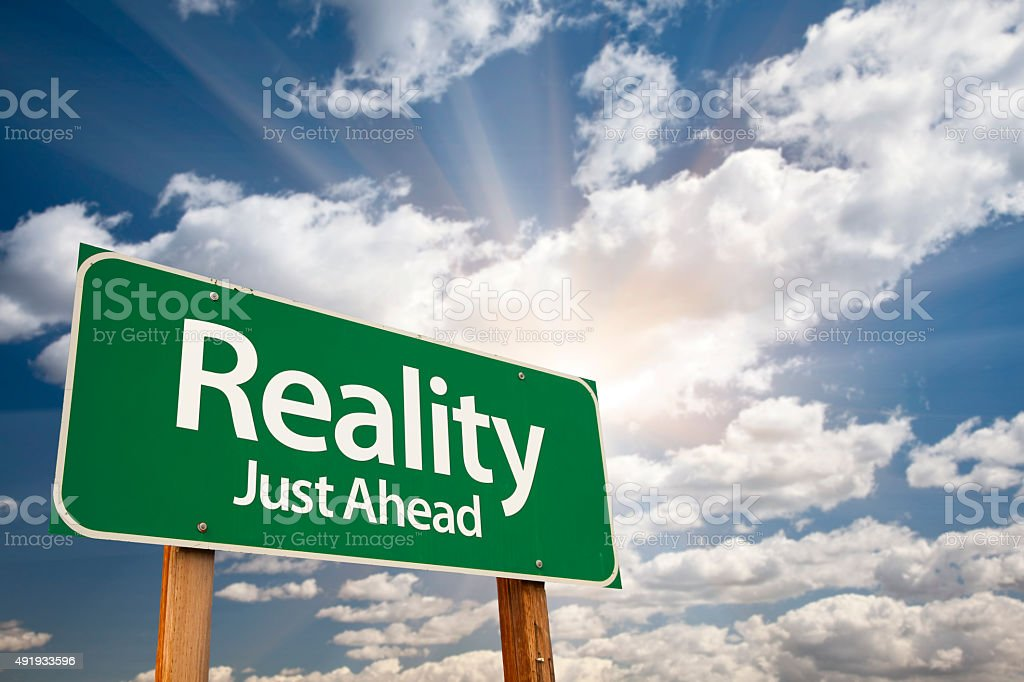 Reality Green Road Sign Over Clouds stock photo