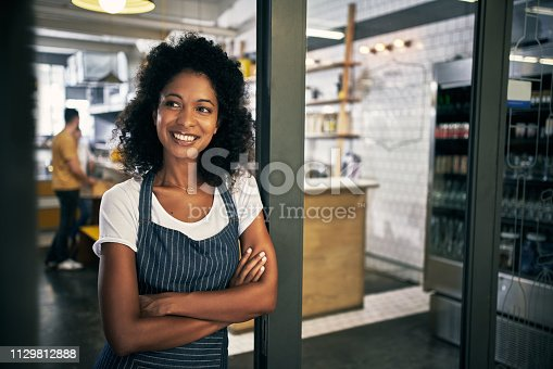 Cropped shot of an attractive young woman standing in the doorway to her coffee shop with her arms folded