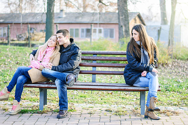 Really hate you A couple of young man and woman teenagers sitting on a bench, embracing, in love and happy at the other end sits a sad alone girl former stock pictures, royalty-free photos & images