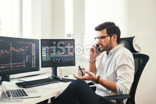 istock Really? Worried bearded businessman or trader in formalwear and eyeglasses is talking with client and gesturing while sitting in modern office 1147352116