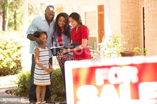 Latin descent realtor shows African descent family a new home to purchase.  Mother, father and daughter.  Real estate sign.  Home in background.  Spring or summer season.