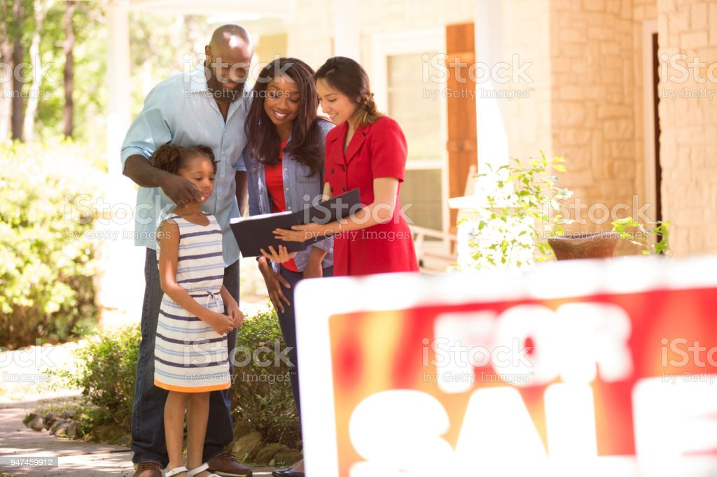 Realtor and family looking at new home to purchase. stock photo