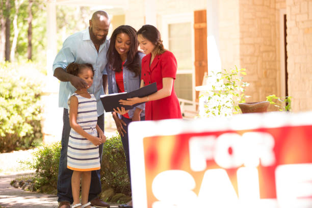 Realtor and family looking at new home to purchase. Latin descent realtor shows African descent family a new home to purchase.  Mother, father and daughter.  Real estate sign.  Home in background.  Spring or summer season. real estate sign stock pictures, royalty-free photos & images