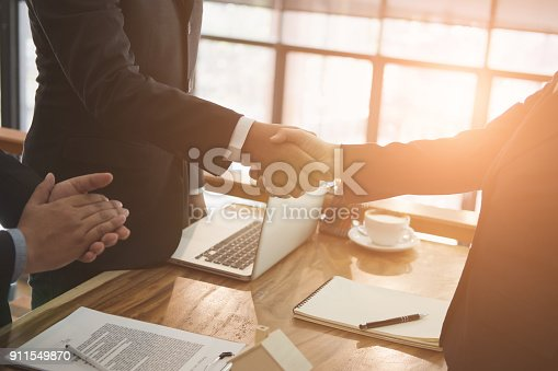 istock realtor & client handshaking. real estate agent shaking hands with customer. sale & purchase property with signing contract document & approved mortgage loan 911549870