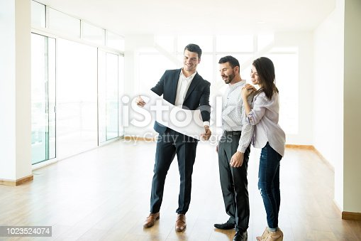 istock Realtor Discussing Apartment Layout With Couple In Empty Room 1023524074
