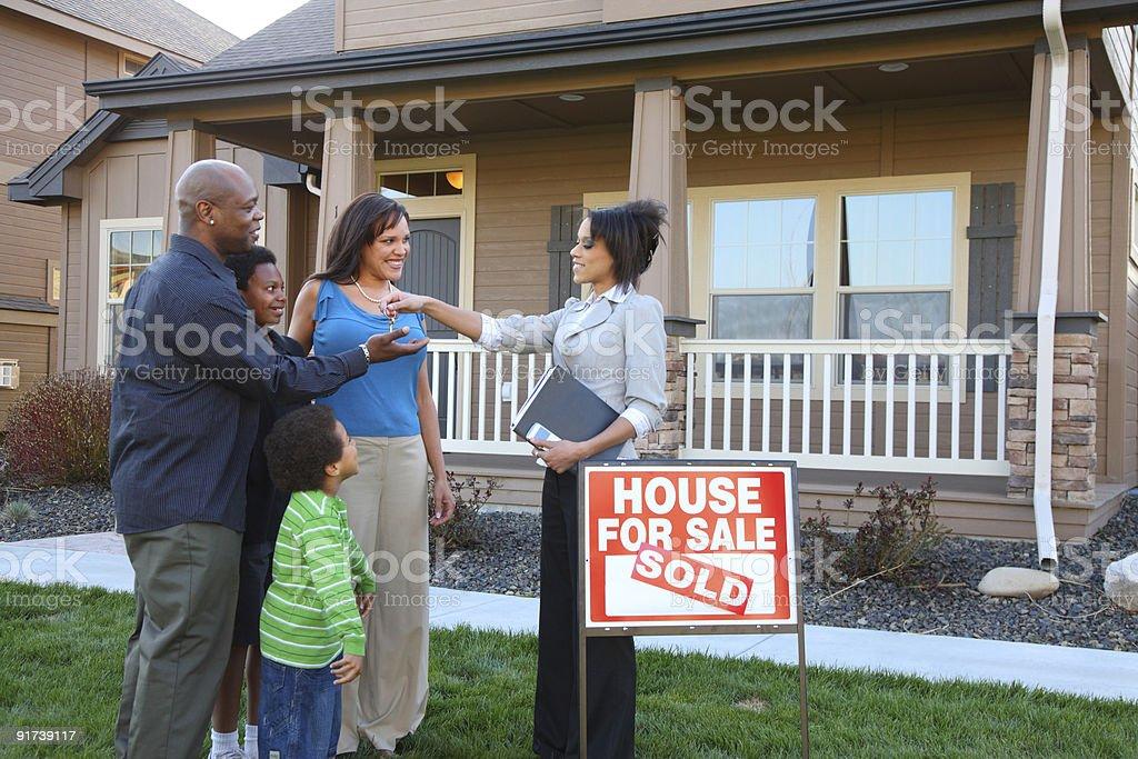 Realtor gives family keys to new home stock photo
