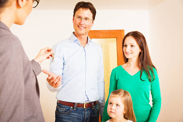 realtor giving customers the key to their new flat stock photo