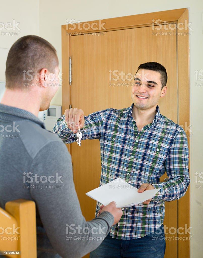 Realtor giving keys to flat owner stock photo
