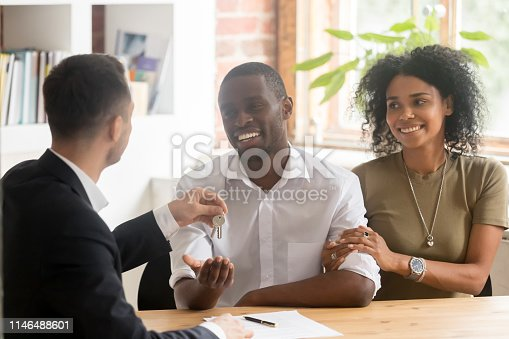 istock Realtor giving keys to new house to african married couple 1146488601