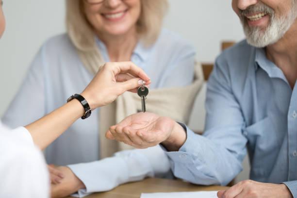 grundstücksmakler geben älteres paar schlüssel zum neuen haus tagung - seniorenwohnungen stock-fotos und bilder