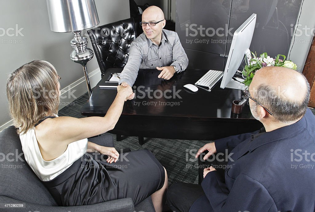 Realtor Greeting a Couple Buying New Home royalty-free stock photo