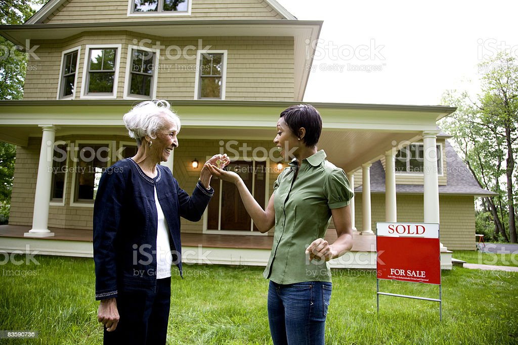 Realtor handing keys to new home owner royalty-free stock photo
