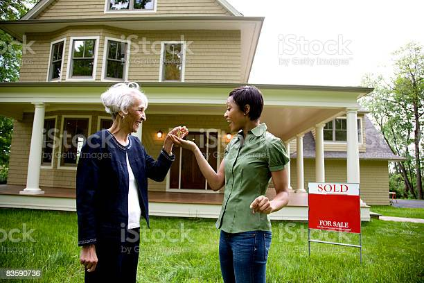 Realtor Handing Keys To New Home Owner Stock Photo - Download Image Now