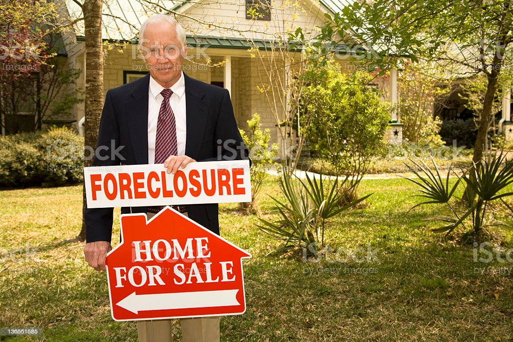 Realtor holds foreclosure real estate sign. Home for sale. royalty-free stock photo