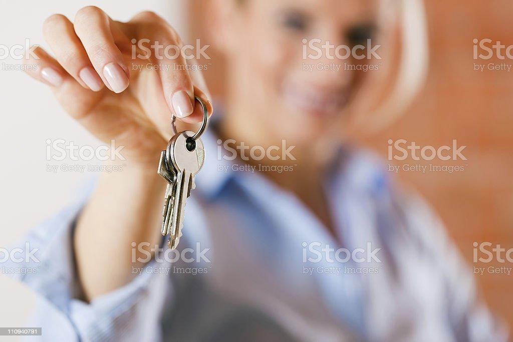 Realtor in empty apartment giving keys stock photo